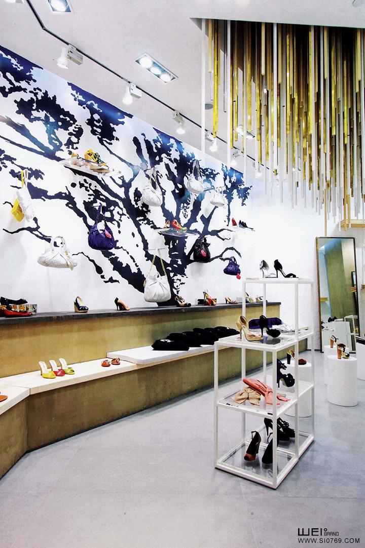 这间位于大街边的旗舰店, 大气的门面设计凸显了 EQIQ高格调的品牌形象。由于地处北方, 北京很长时间天气都会比较凉, 人们逛商场的时间多于逛街。考虑到这一点, 设计师在门口加入了一些创意性的装饰来吸引客人, 如在墙上悬挂一副有EQIQ商标的手绘树, 还有用不同物料制成的吊垂等。另外, 不同长度的悬挂木条, 也是这间旗舰店比较有意思的装饰。当然,还少不了本店的独有元素,衣饰架、木墙、以及selected co11ection的金色衣饰架,在加入这些 新元素的同时, 也能保持店内原有的特色。 This fl