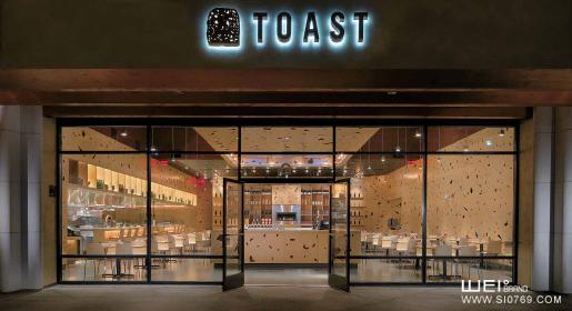 吐司餐厅供应可口的一日三餐。它是位于旧金山北部纳瓦托的新汉密尔顿城商场的第二家分店。进入面包房就像进入一大片面包中,又像畅游在闪闪发光的香槟中。创造了这个内部世界巨大发面饼效果的其实是颗粒饭,它带有自由形状的孔洞,覆盖了所有的表面墙壁、顶棚、家具都包裹在这个起泡的像面包一样的空间内。  低矮的被覆盖的入口,通过悬挂在酒吧上方的悬柱,过得到室内空间。柱内可储存玻璃杯。吧台的立方体结构上下对称 三个色面都可以提供座位。柜台后面的顶棚下落到主用餐厅区。首先是大型的公用桌子,然后是较小的桌子可卡位,开放式的厨房
